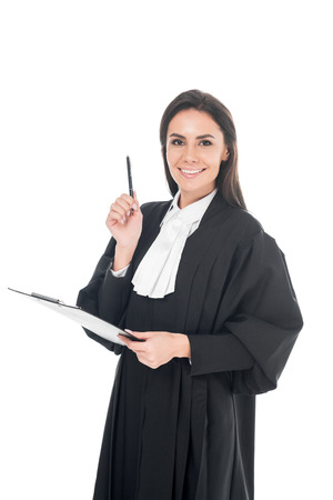 Smiling judge in judicial robe holding clipboard and pen isolated on white Reklamní fotografie