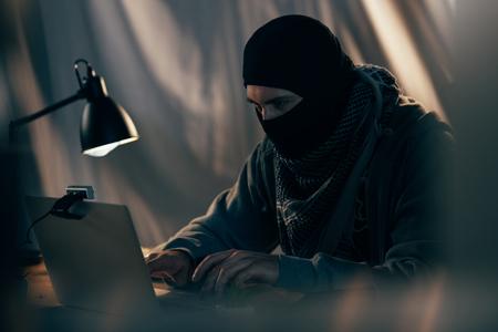 Terrorist in black mask typing on laptop keyboard in room Stock Photo