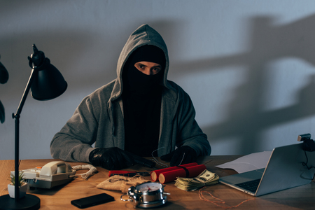 Criminal in mask with gun and dynamite sitting at table and looking at camera Stock Photo