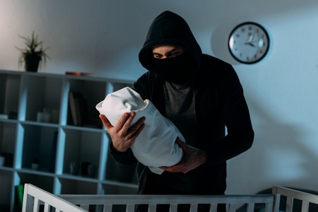 Kidnapper in mask and black hoodie standing near crib and holding infant child