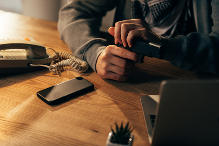 Partial view of criminal sitting at table and holding gun Stock Photo