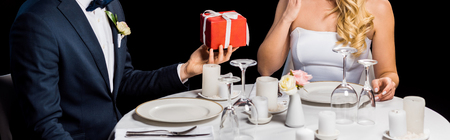 panoramic shot of groom presenting red gift box to bride, while sitting at served table isolated on black