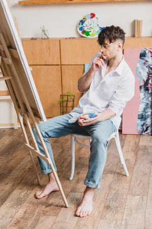 handsome artist in white shirt and blue jeans looking at canvas on easel