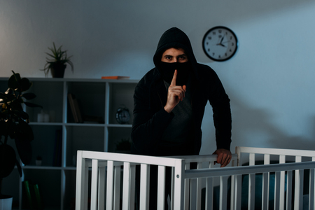 Kidnapper in mask and black hoodie showing hush sign beside crib