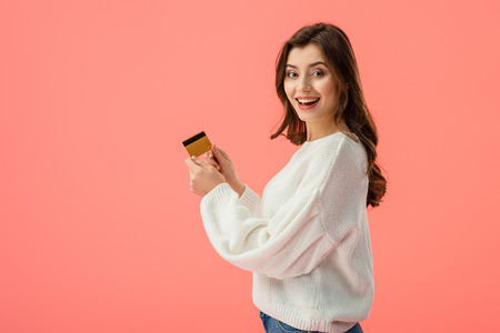 happy brunette girl holding credit card isolated on pink