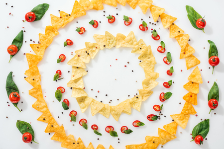 top view of tasty nachos, spices and sliced chili peppers with basil and ripe cherry tomatoes