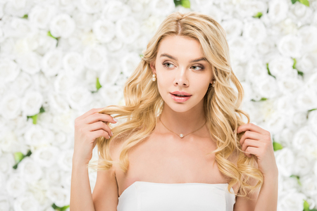 beautiful young woman touching blonde hair on white floral background 스톡 콘텐츠