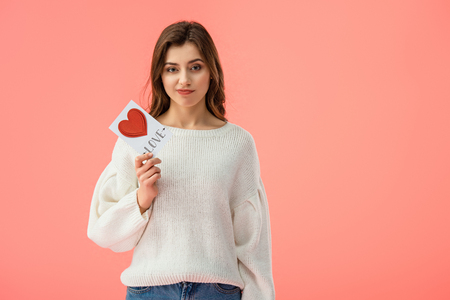 sad young woman holding card with love lettering isolated on pink