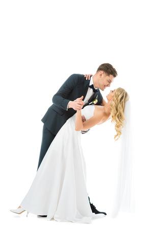 Novio guapo en traje elegante bailando con hermosa novia en vestido de novia aislado en blanco Foto de archivo