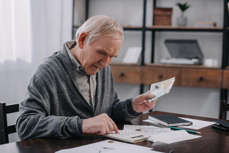senior man in casual clothes sitting at table with paperwork and using calculator while counting money Stock Photo