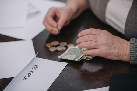 cropped view of couple woman counting money near envelope with 'roth ira' lettering Stock Photo - 120135266