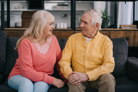 senior couple in casual clothes sitting on couch and looking at each other in living room Stock Photo