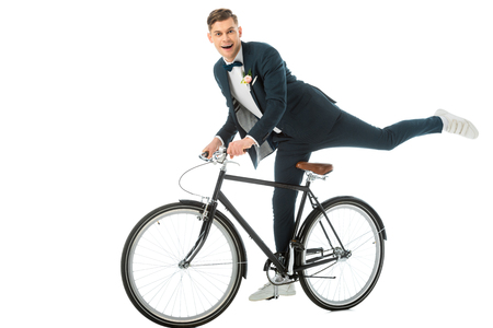 cheerful groom in elegant suit making stunts on bike isolated on white Stock Photo