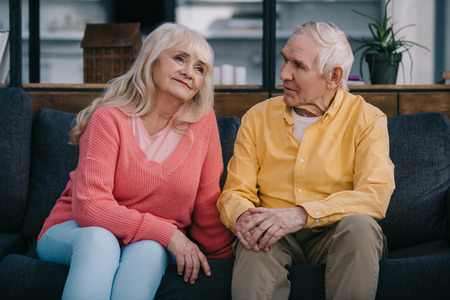senior couple in casual clothes sitting on couch in living room