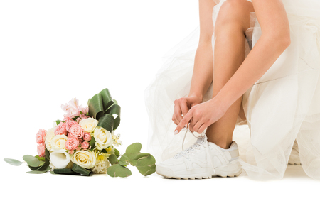cropped view of woman tying shoelaces on sneakers, and wedding bouquet isolated on white 스톡 콘텐츠