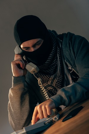 Terrorist in black mask talking on telephone in room Фото со стока - 120135519