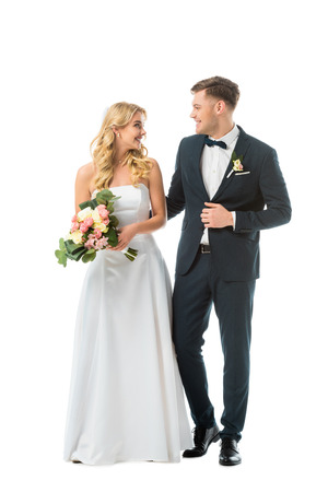 pretty bride in wedding dress, and handsome groom in elegant black suit looking at each other isolated on white Stock Photo