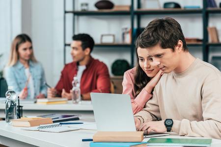 Lächelnde Studenten, die an Schreibtischen sitzen und einen Laptop benutzen, während sie im Klassenzimmer lernen