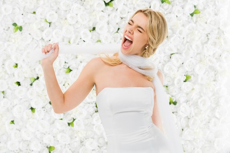 excited young woman winding bridal veil around neck on white floral background