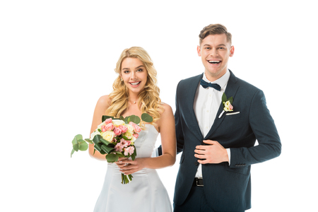 smiling bride with beautiful wedding bouquet, and groom in elegant black suit isolated on white Stock Photo