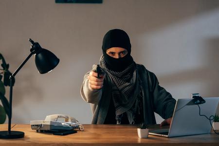 Angry terrorist in black mask aiming gun at camera