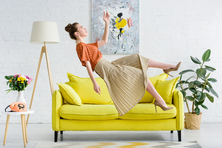 side view of elegant young woman levitating in air in living room Stok Fotoğraf