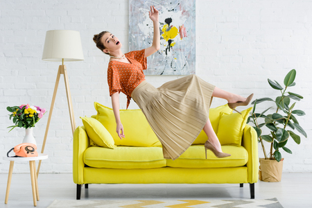 side view of shocked elegant young woman levitating in air in living room