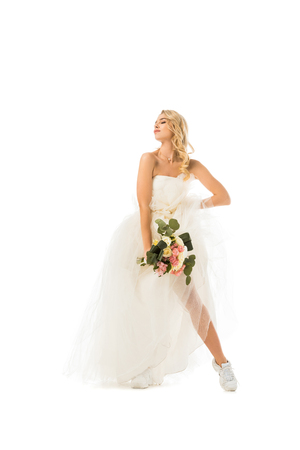 beautiful young woman posing in wedding dress and sneakers isolated on white