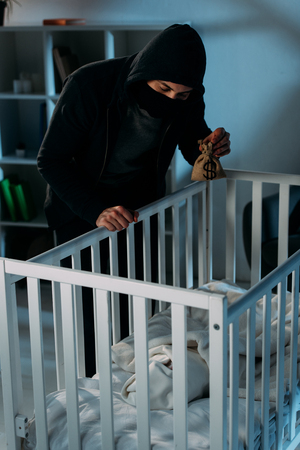 Criminal in mask holding money bag and looking in crib Stock Photo