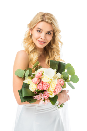 beautiful bride holding wedding bouquet and looking at camera isolated on white