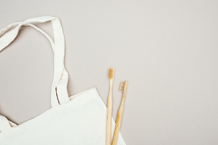 wooden toothbrushes and white cotton bag on grey background