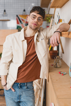 selective focus of handsome artist  in eyeglasses leaning on wooden shelve in painting studio