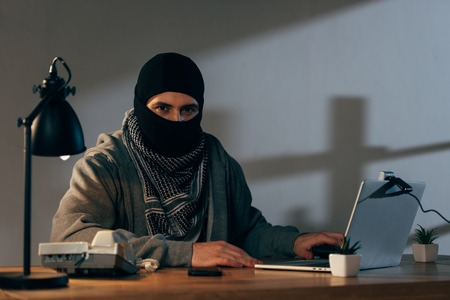 Terrorist in mask and keffiyeh scarf using laptop in room Stock Photo