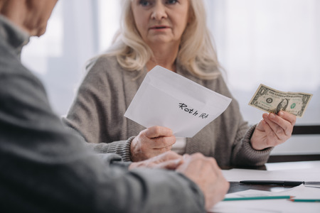 cropped view of senior couple holding envelope with 'roth ira' lettering and dollar banknote Stock Photo - 120136279