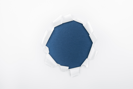 ragged hole in textured white paper on dark blue background Фото со стока