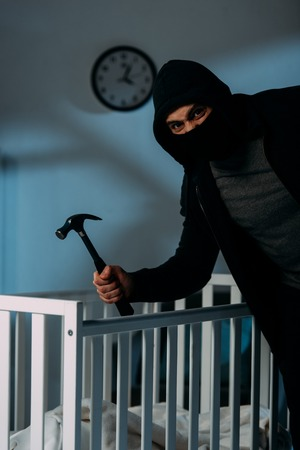 Angry criminal in mask standing near crib and holding hammer