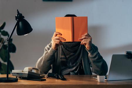 Terrorist in keffiyeh scarf with gun reading book in room