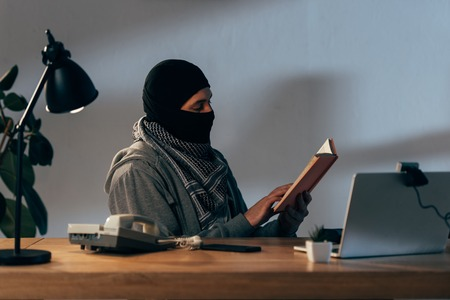 Concentrated terrorist in black mask sitting at table and reading book