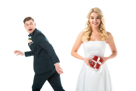 happy beautiful bride holding gift box, while tricky groom imitating running away isolated on white