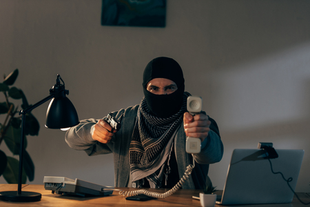 Aggressive terrorist in mask holding handset and aiming gun
