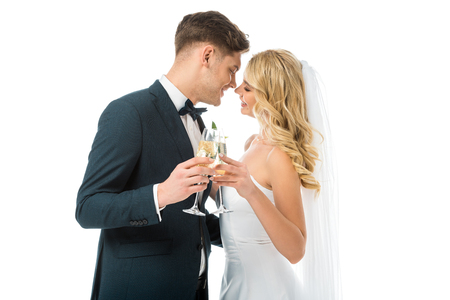 happy bride and groom clinking glasses of champagne while standing face to face isolated on white