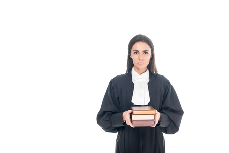 Serious judge in judicial robe holding books isolated on white