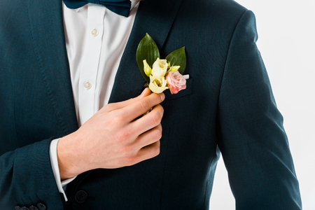 cropped view of bridegroom in black costume jacket with boutonniere isolated on white Фото со стока