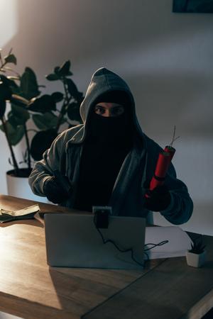 Terrorist with dynamite and laptop aiming gun at camera Stock Photo
