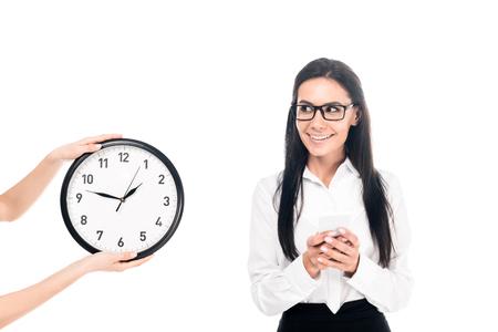 Lächelnde Geschäftsfrau mit Brille, die in der Nähe der Uhr steht, isoliert auf weiss