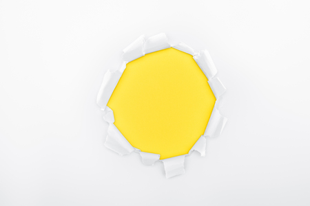 torn hole in white textured paper on yellow background