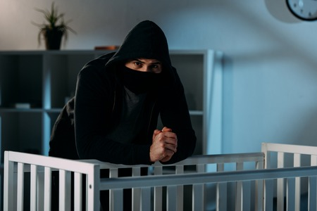 Kidnapper in black mask standing beside crib and looking at camera