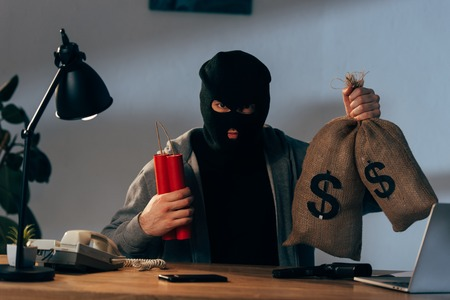 Terrorist in mask holding dynamite and money bags in room