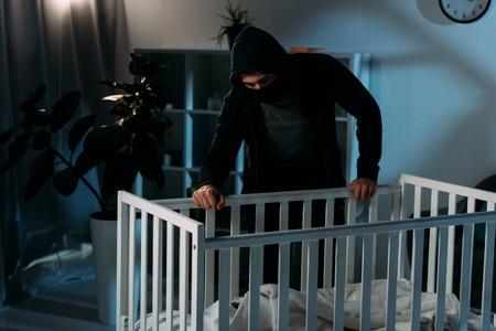 Kidnapper in mask and hoodie looking in crib in dark room
