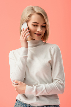 attractive blonde woman talking on smartphone isolated on pink